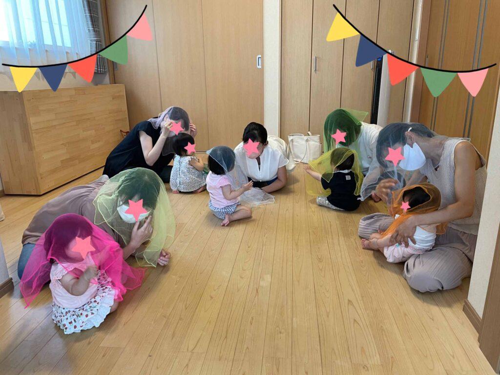 リトミックスカーフを使ったレッスンを受ける親子たち