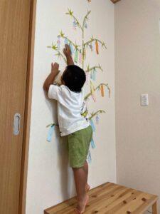 めいいっぱい背伸びして笹に短冊を飾る子ども